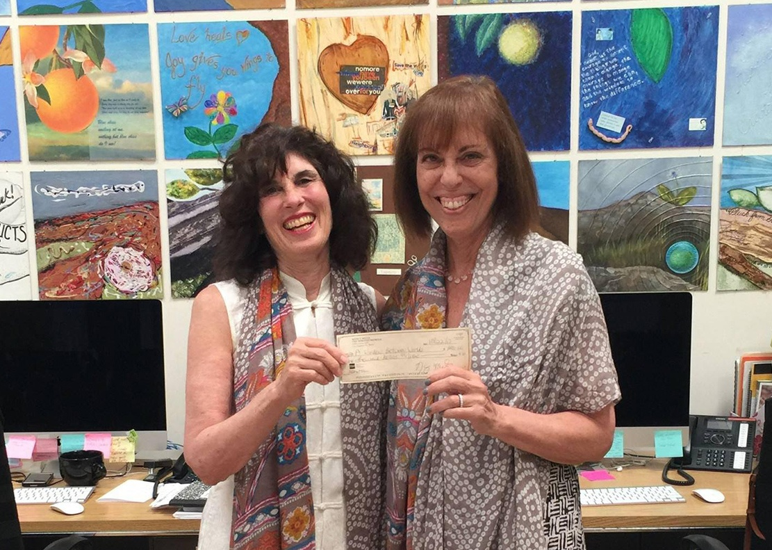 Nancy Mills gifting a check to Audrey Salzburg, Chief Executive Officer of a A Window Between Worlds (AWBW).jpg