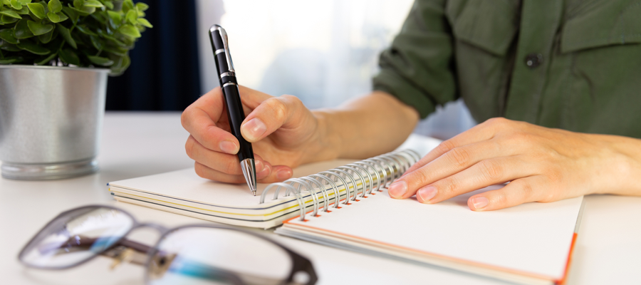 man journaling in notebook with a pen
