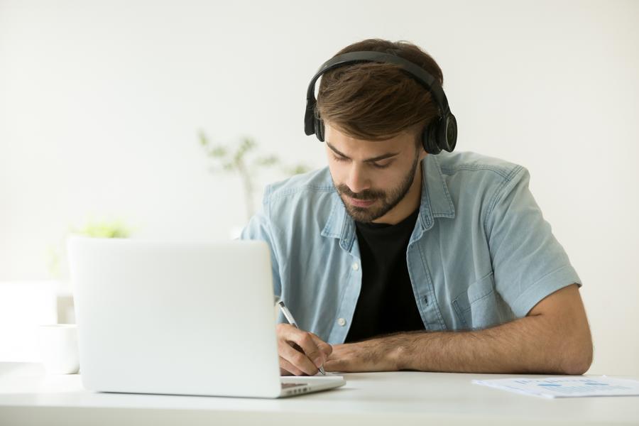 man-journaling-with-headphones