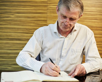older-man-journaling-in-a-large-journal