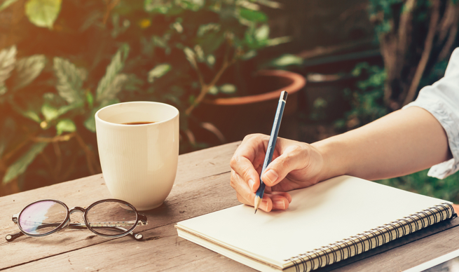 woman-journaling-with-large-cup-coffee